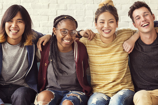 Four youth smiling and sitting together