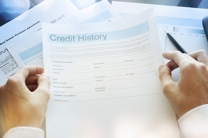 Hands holding a credit history paper